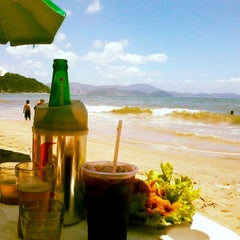 Photo taken at Praia de Laranjeiras by Fernanda F. on 11/11/2012