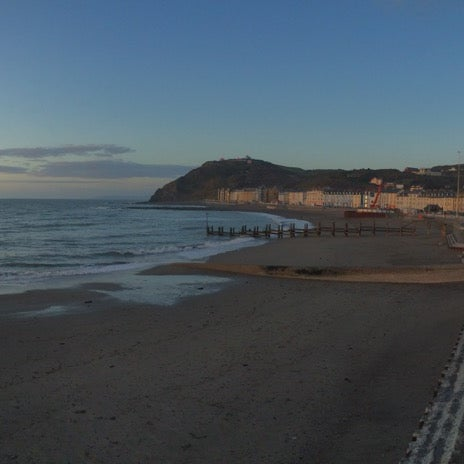 Photo taken at Aberystwyth Beach by Elif E. on 3/27/2015